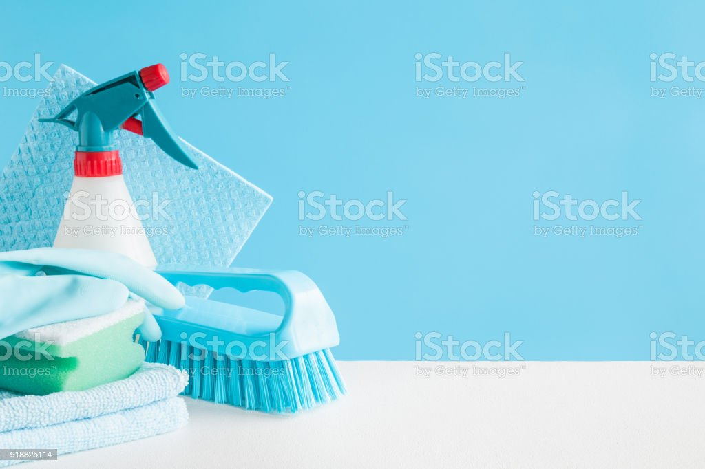 Cleaning set for different surfaces in kitchen, bathroom and other rooms. Empty place for text or logo on blue background. Cleaning service concept. Early spring regular clean up. Front view. stock photo