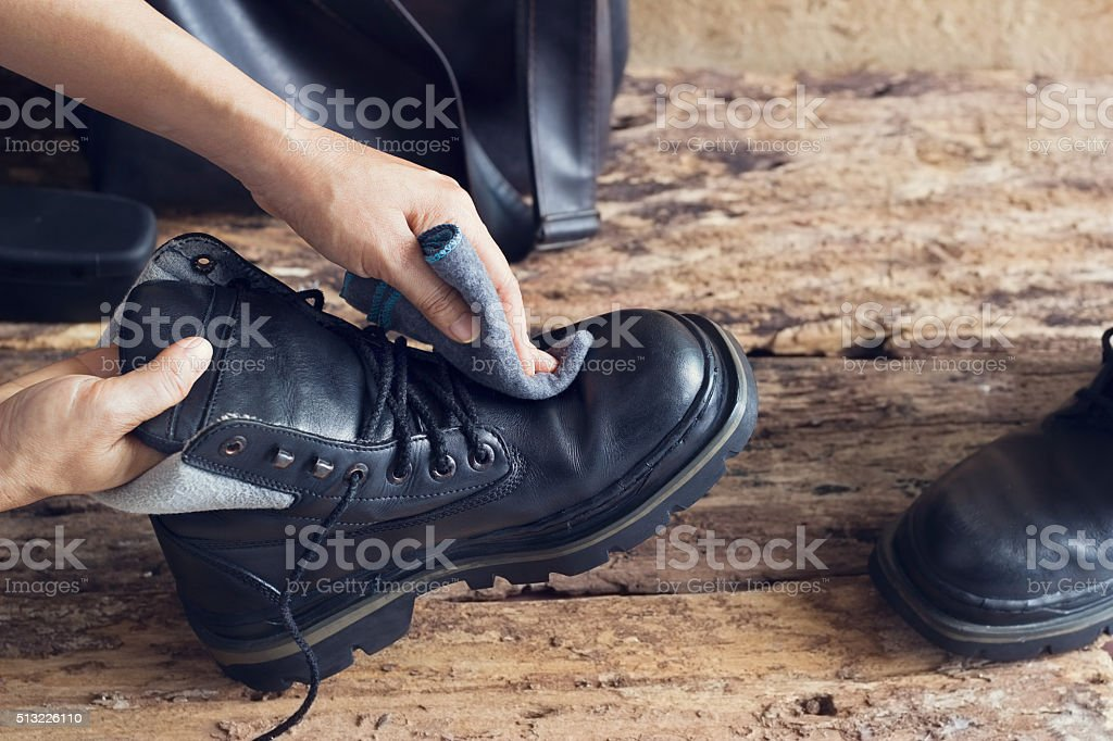 Cleaning shoes on wooden background stock photo