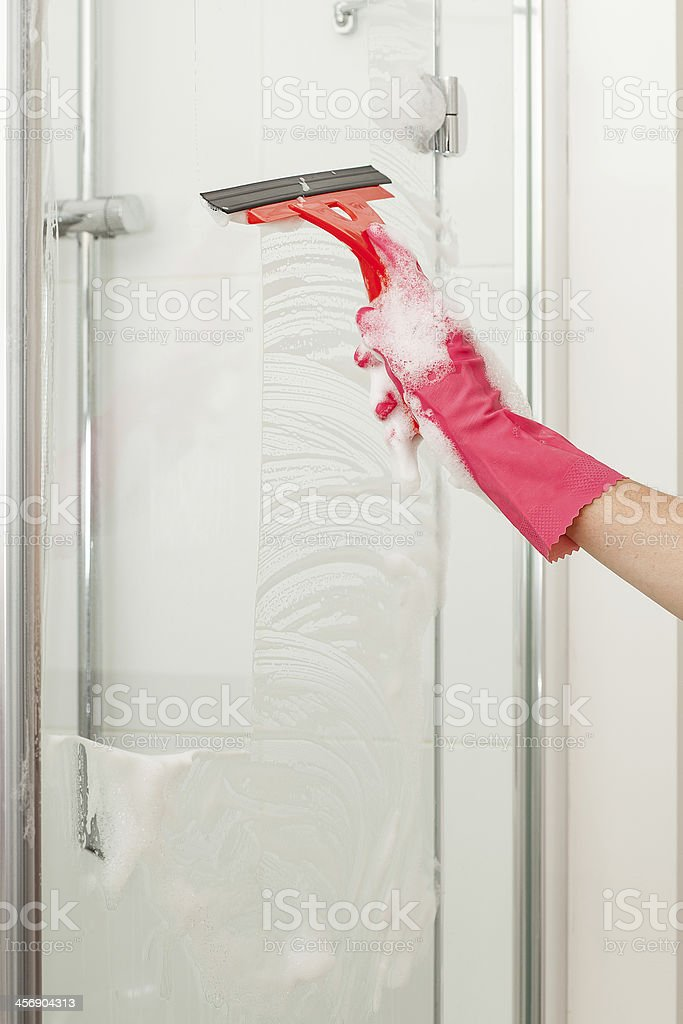 Cleaning shower with a squeegee stock photo