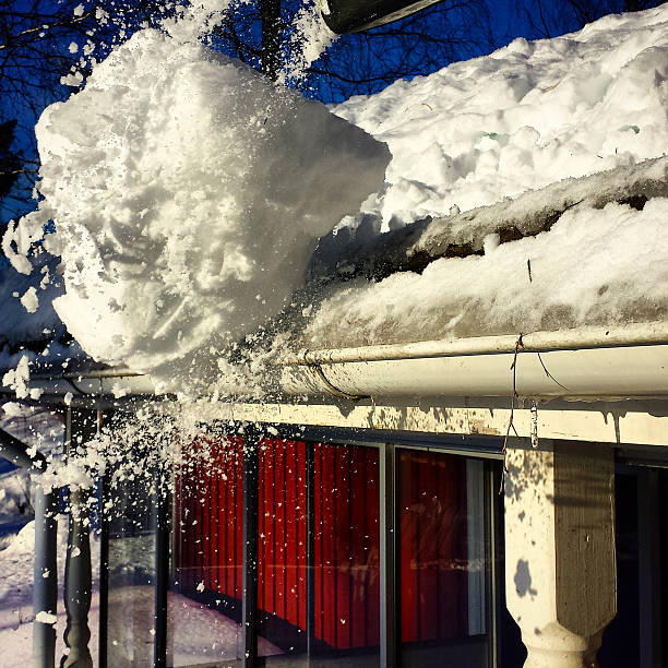 Cleaning snow from roof stock photo