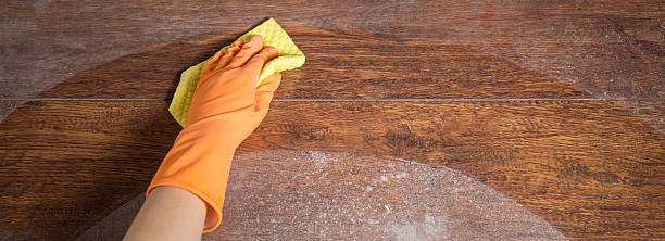 Cleaning soiled parquet in gloves stock photo