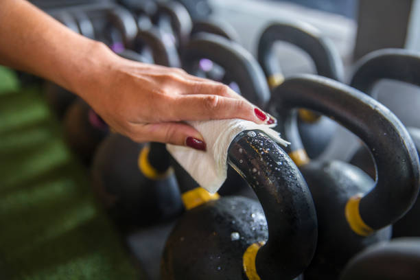 Cleaning sport equipment precautions Covid 19 spreading at gym stock photo