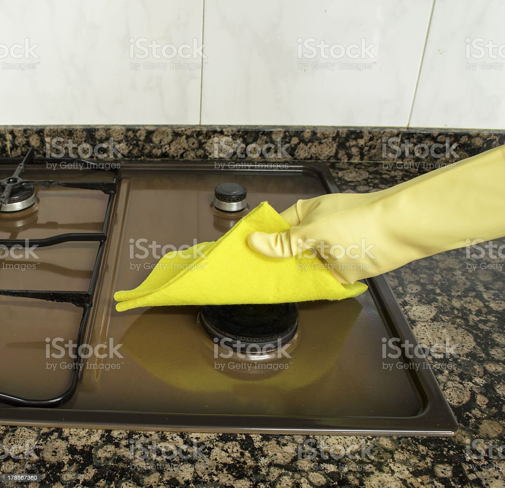 cleaning stove with yellow cloth royalty-free stock photo