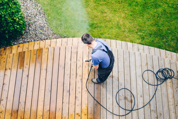 cleaning terrace with a power washer - high water pressure cleaner on wooden terrace surface - forza foto e immagini stock