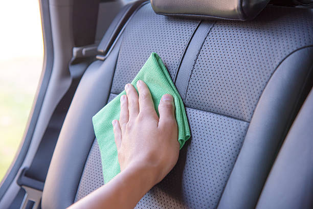 Cleaning the car interior Hand cleaning the car interior with green microfiber cloth vehicle seat stock pictures, royalty-free photos & images