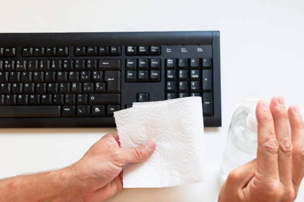 Cleaning the computer keyboard with antiseptic gel and a cloth before using it stock photo