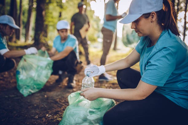 Cleaning the environment together Group of people, cleaning together in public park, saving the environment. environmental cleanup stock pictures, royalty-free photos & images