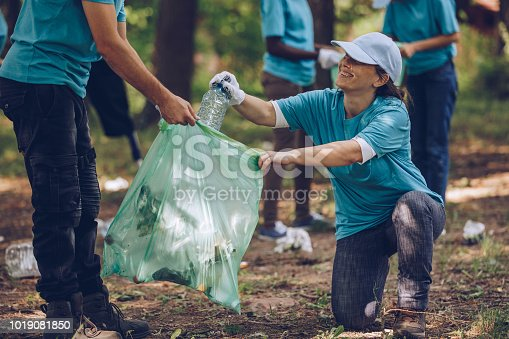 Group of people, cleaning together in public park, saving the environment.