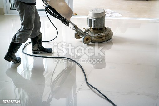 Photo of a man cleaning the floor with a cleaning machine.