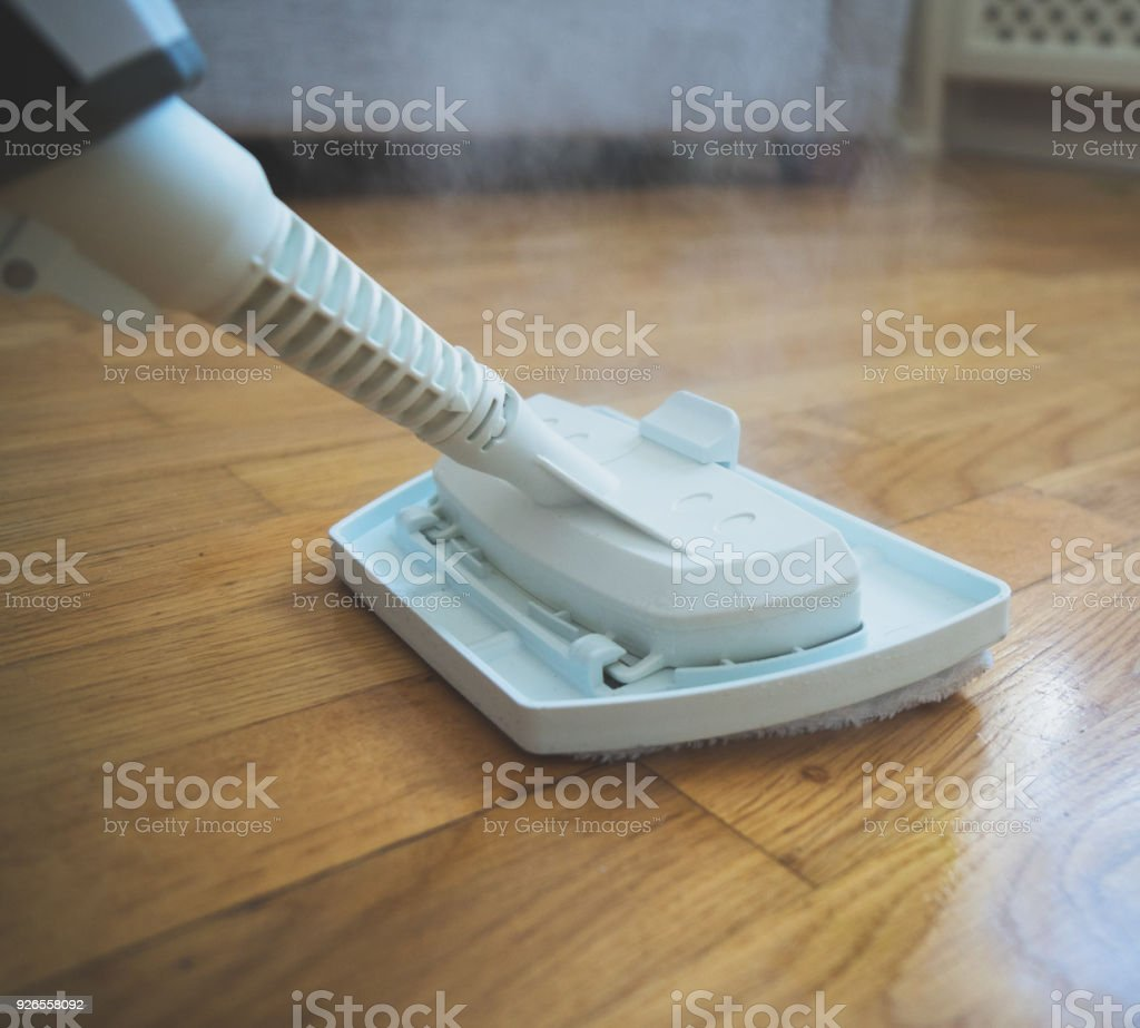 Cleaning the floor with a dry steam cleaner. stock photo