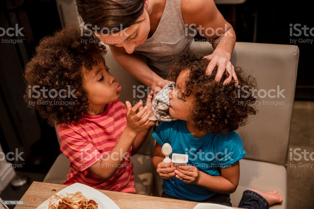 Mum is cleaning food off the face of her child a sibling helps