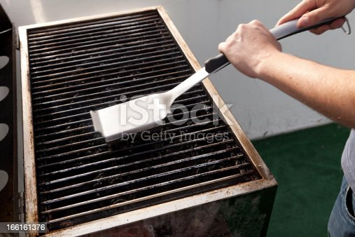 Getting the grill ready for some cooking - scraping old fat with the grill brush, blurred by the swift movements of cleaning.