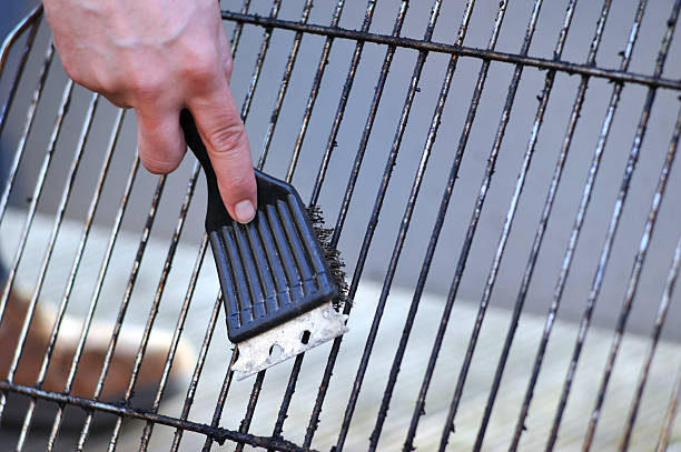 cleaning the grill with scrubber - Grillbürste human hand is cleaning the grill rost with scrubber scrubbing brush stock pictures, royalty-free photos & images