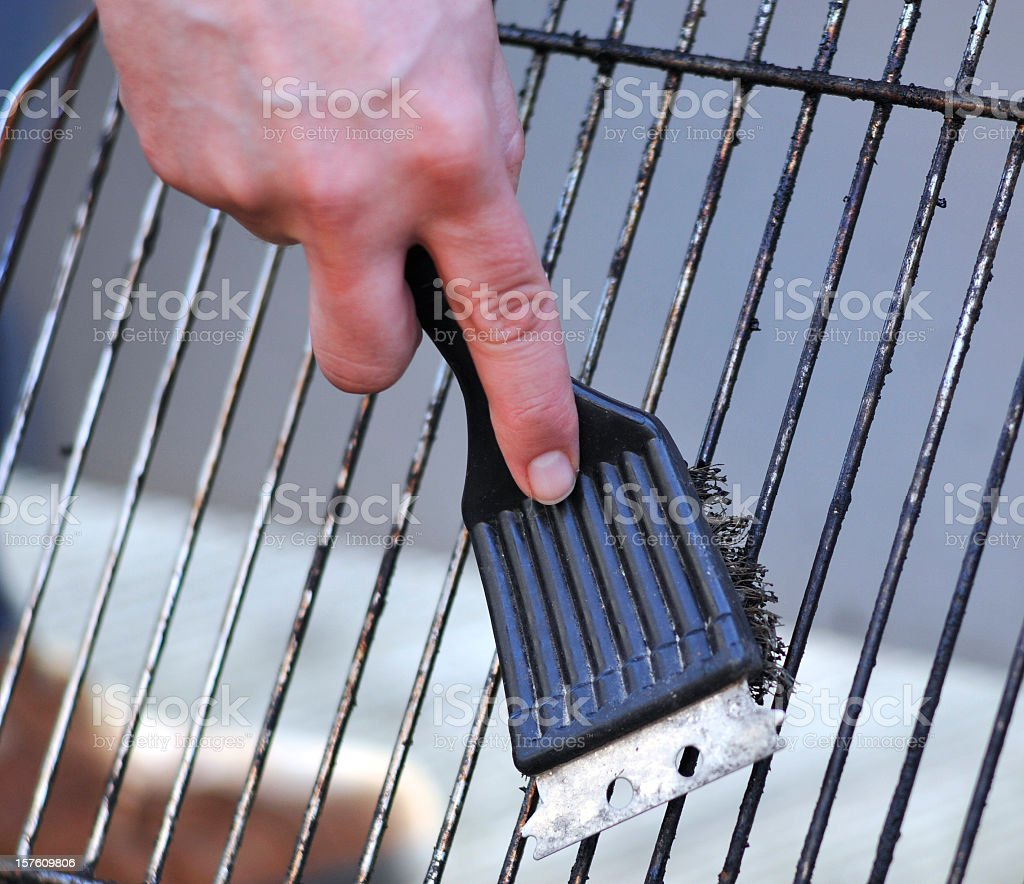 cleaning the grill with scrubber stock photo