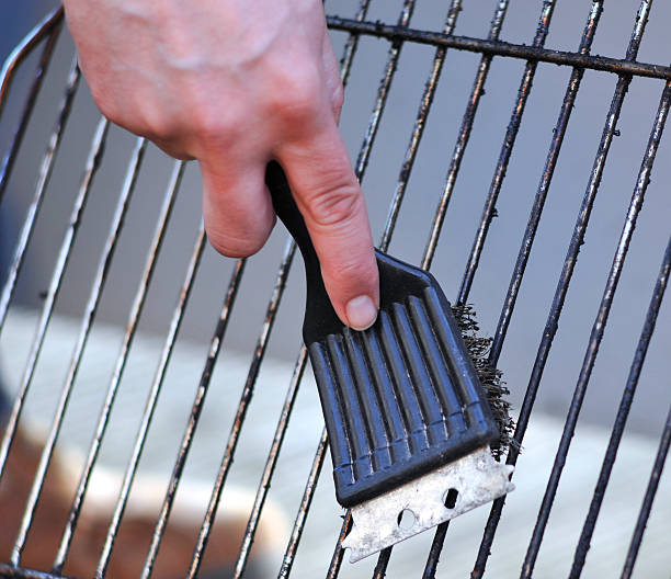 cleaning the grill with scrubber human hand is cleaning the grill rost with scrubber scrubbing brush stock pictures, royalty-free photos & images