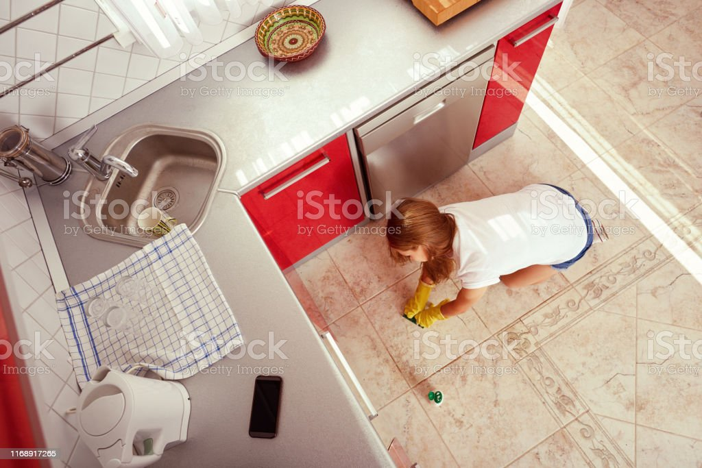 High angle viewpoint of girl cleaning the kitchen floor