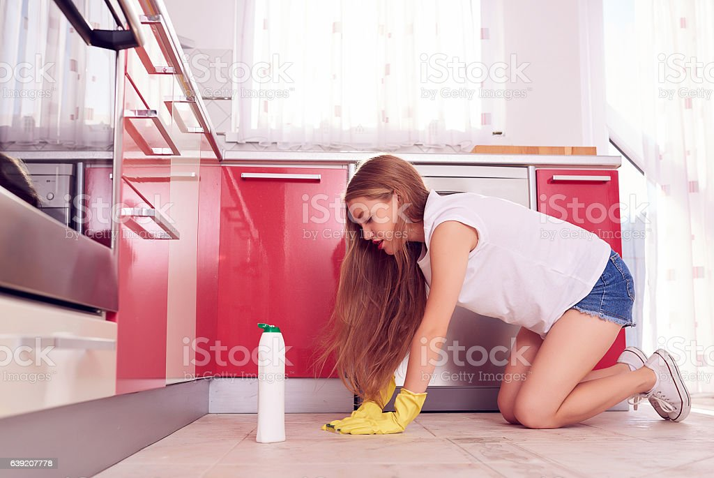 side view of young woman in her knees cleaning the kitchen...