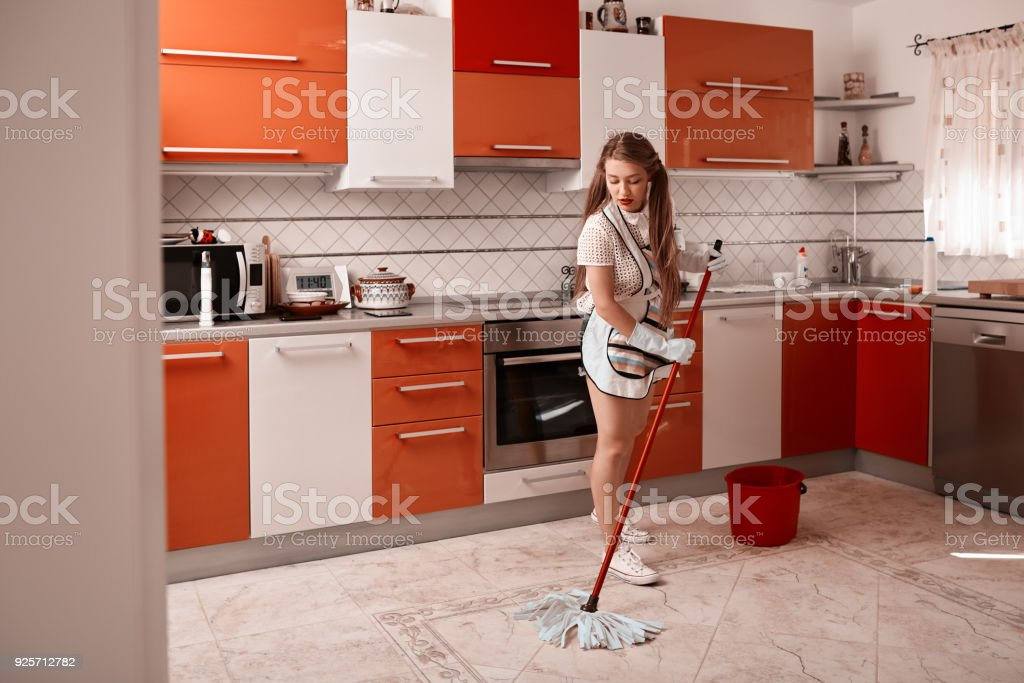 lifestyle shot of young woman in the kitchen cleaning the floor with...