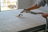 Photo of a person cleaning a mattress.