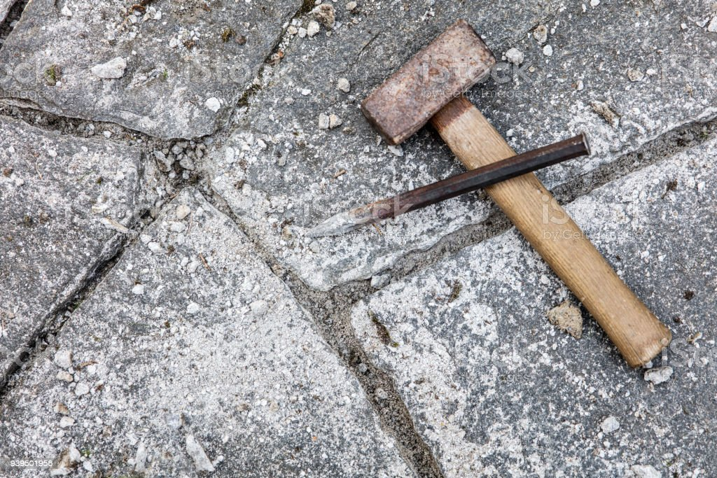 cleaning the mortar joints of a flagstone floor with stone mason tools, like hammer and chisel, preparing for fresh grouting stock photo