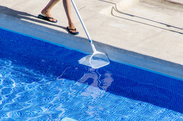 reinigung der pool-seite mit einem netz - flip flops reparieren stock-fotos und bilder