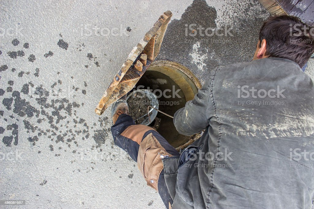 cleaning the sewers, blocked drain cleaning stock photo