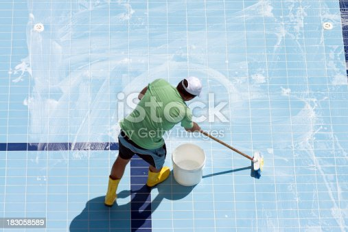 Man cleaning the tiled floor of swimming-pool.