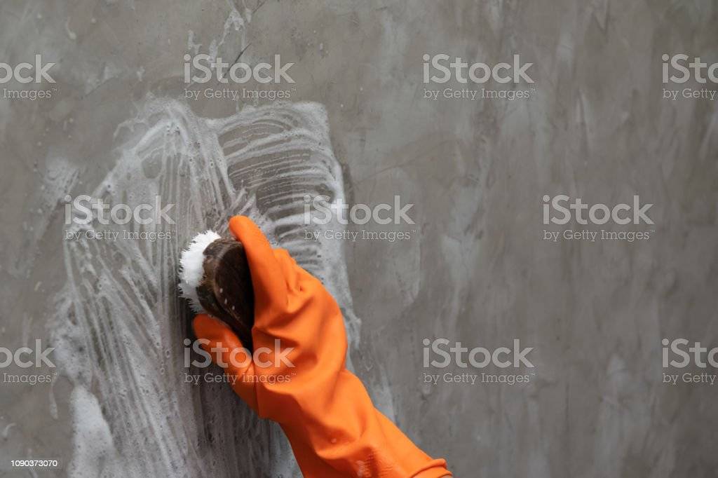 Woman\'s hand wearing orange rubber gloves is used to convert scrub...