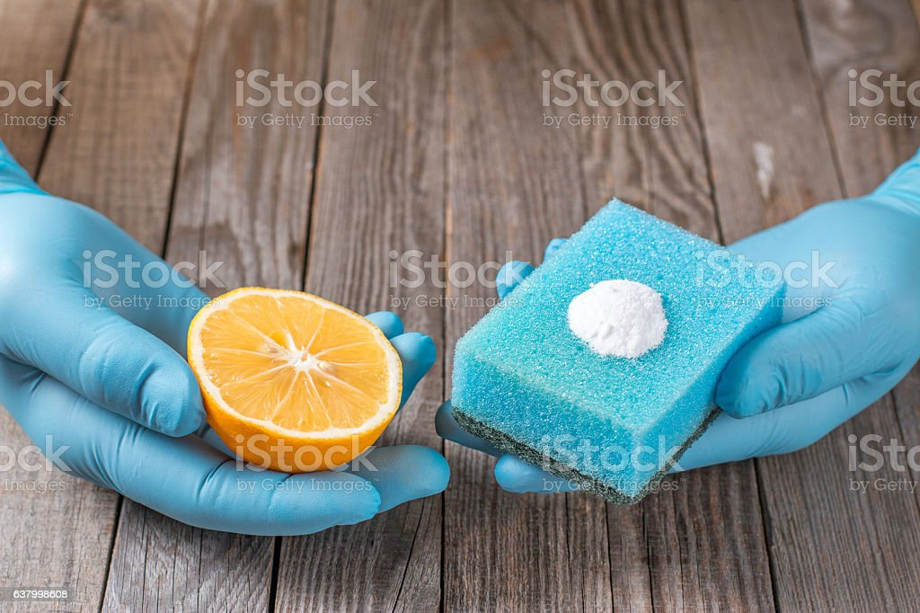 cleaning tools and sodium bicarbonate in hand on wooden table stock photo