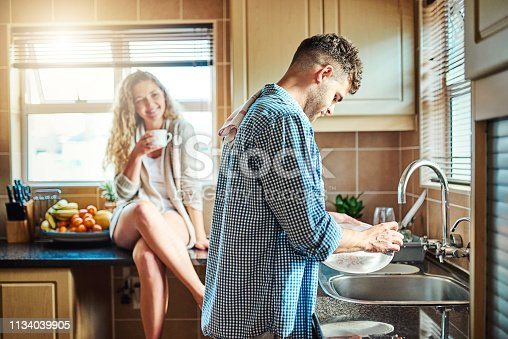Shot of a woman keeping her husband company while he does the dishes