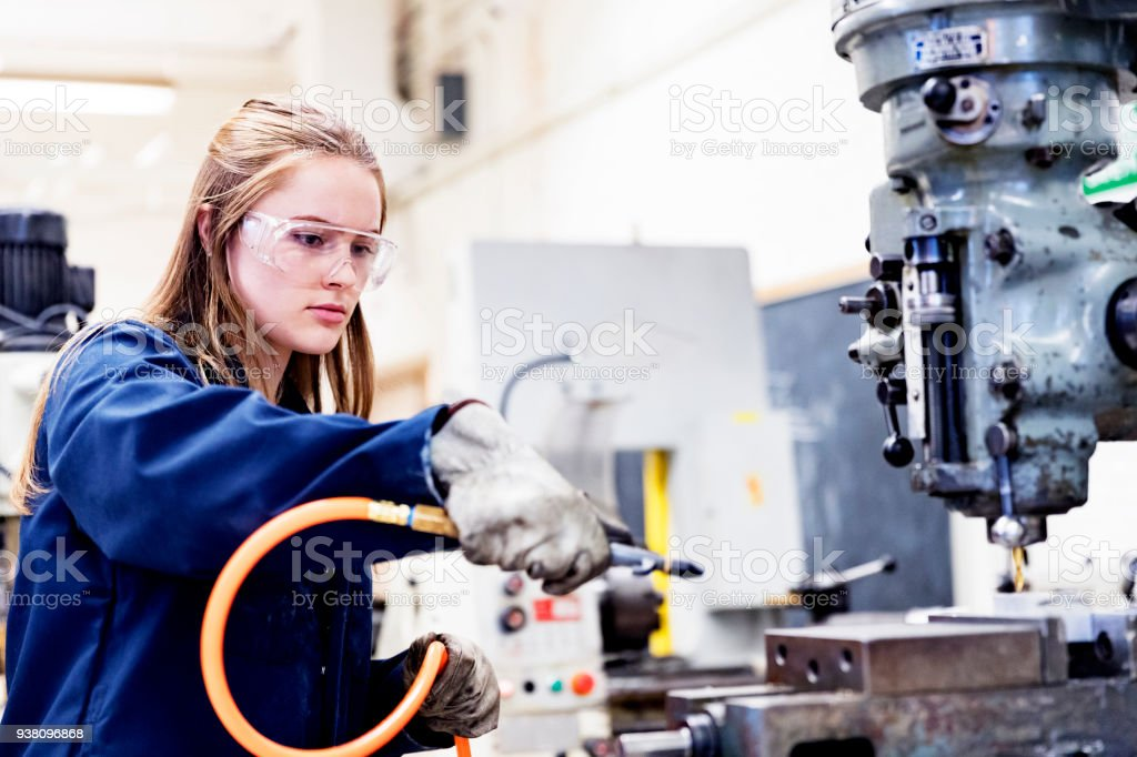 Female STEM student operating compressed air to clean up the metal...