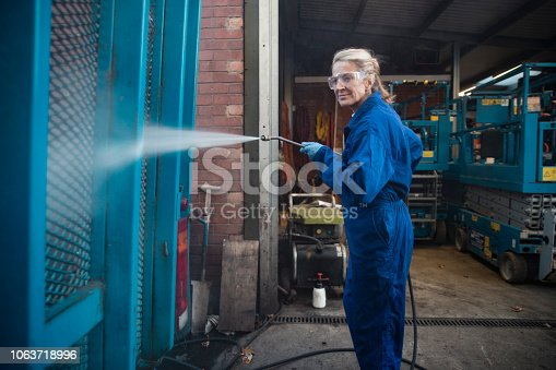 A side-view shot of a female manual worker cleaning a vehicle exterior with a high-pressure​ water hose.