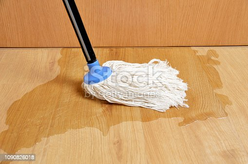 Person cleaning water from a broken pipe on a laminated parquet