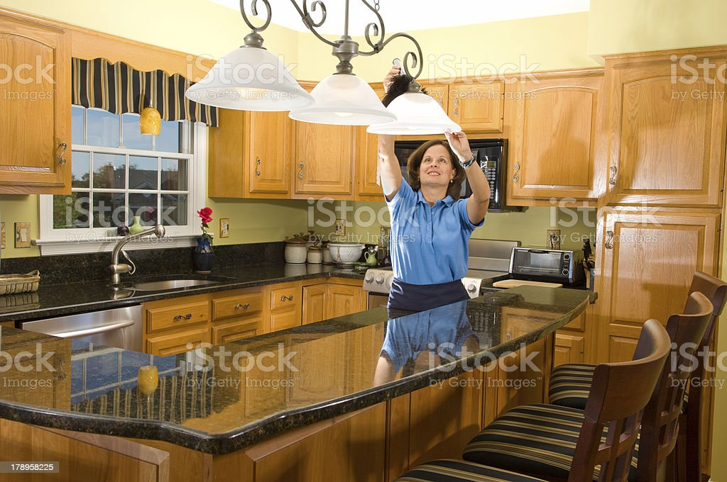 Cleaning Woman in Luxury Kitchen stock photo