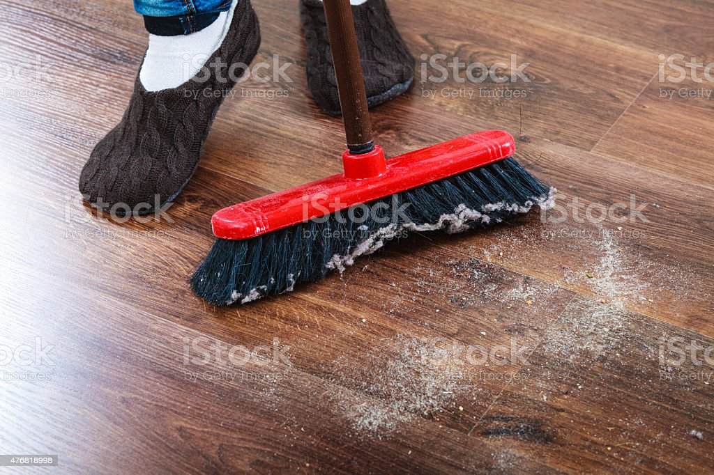 Cleaning woman sweeping wooden floor stock photo