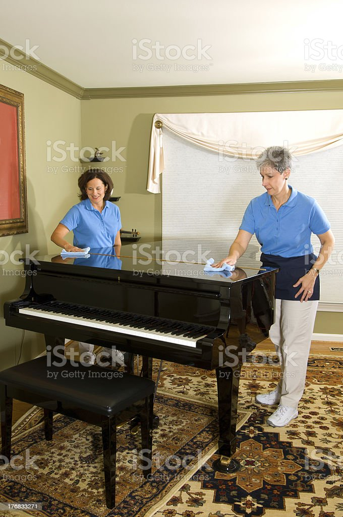 Cleaning women dust a baby grand piano royalty-free stock photo
