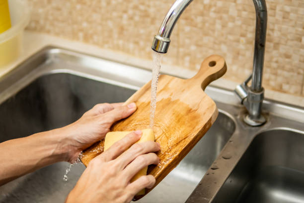cleaning wood cutting board in kitchen sink - разделочная доска стоковые фото и изображения