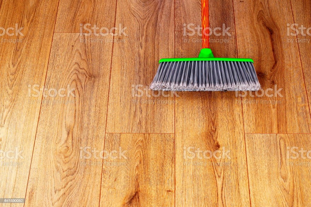 cleaning wooden floor with green plastic broom stock photo