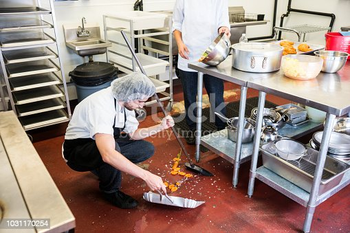 Two real food service professionals cleaning up some spilled food from the floor of a commercial kitchen. Promptly cleaning-up trash and debris in a restaurant or commercial kitchen is important for food safety and personal safety. A concept for safety in the food service industry.