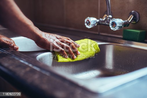 Cropped shot of an unrecognizable man wiping the kitchen sink with a cloth after washing his hands at home