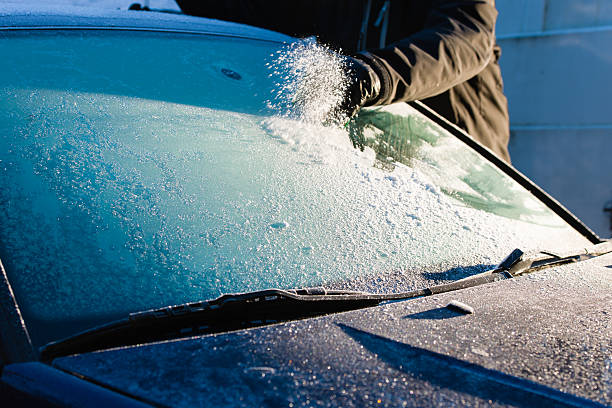 cleans frozen windshield - weather stock photos and pictures