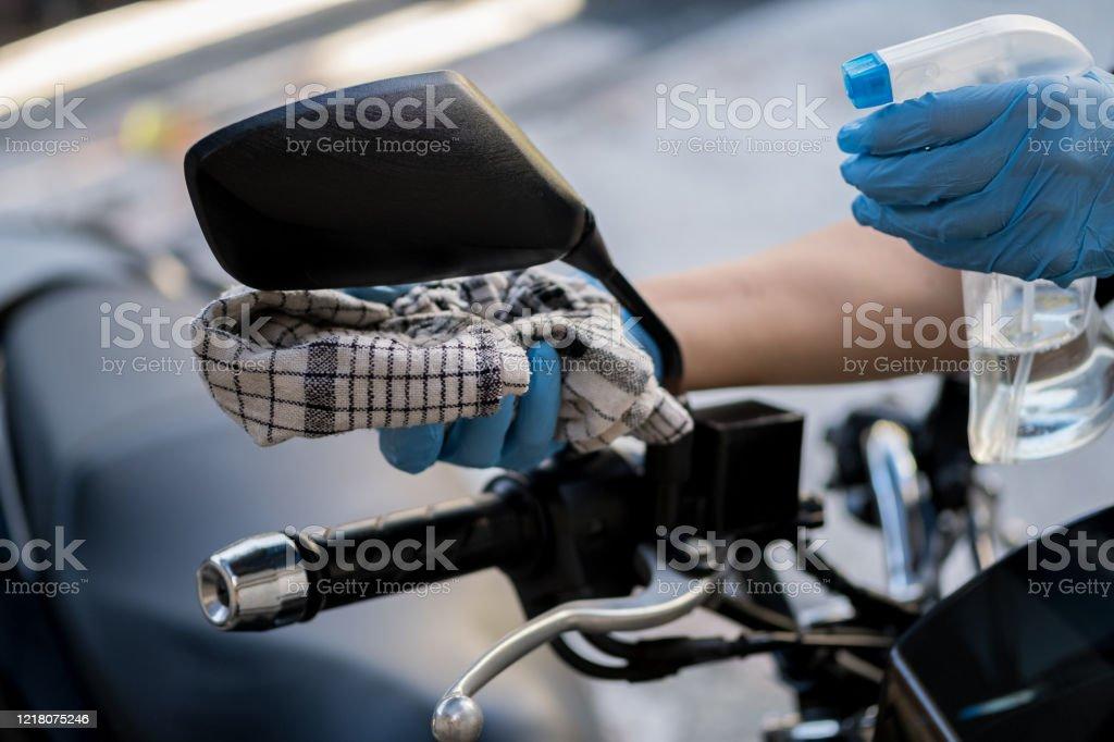 Limpieza del interior de la bicicleta y pulverización con líquido de desinfección. Manos en guante protector de goma desinfectando moto scooter vihicle para la protección contra la enfermedad de corona virus - Foto de stock de Bacteria libre de derechos