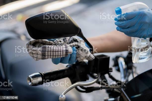 Limpieza Del Interior De La Bicicleta Y Pulverización Con Líquido De Desinfección Manos En Guante Protector De Goma Desinfectando Moto Scooter Vihicle Para La Protección Contra La Enfermedad De Corona Virus Foto de stock y más banco de imágenes de Motocicleta