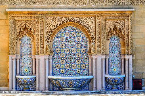 A traditional moroccan fountain with three bowls.  This water feature with brass spouts is found at the King Mohammed mausoleum in Rabat, Morocco where it is decorated in a traditional moroccan style using mosaic mulit-colored tiles