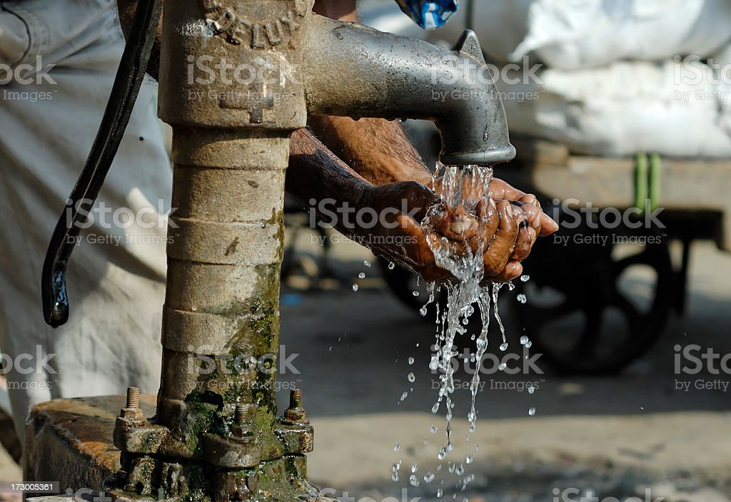 Cleansing hands by way of metal water pump  stock photo