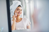 Shot of a beautiful young woman cleaning her face with cotton wool in the bathroom at home