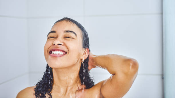 Cleansing my mind and body in warm waters Shot of an attractive young woman taking a shower inside her bathroom at home wet hair stock pictures, royalty-free photos & images