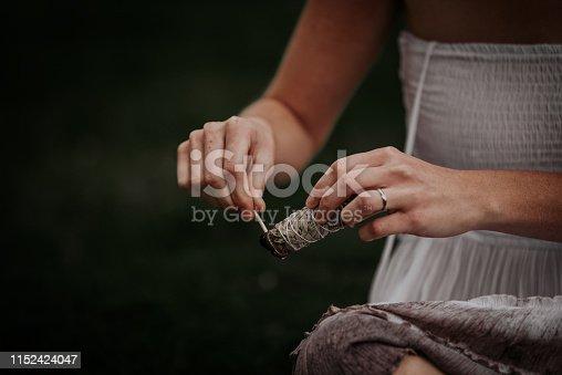 Woman in white dress burns sage