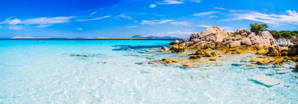 chiara incredibile acqua di mare di colore azzurro con rocce granitiche nella spiaggia di capriccioli, sardegna, italia - sardegna foto e immagini stock