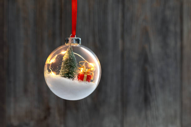 clear ball ornament  with christmas tree,  small gift and christmas light inside. - vintage ornaments stock photos and pictures
